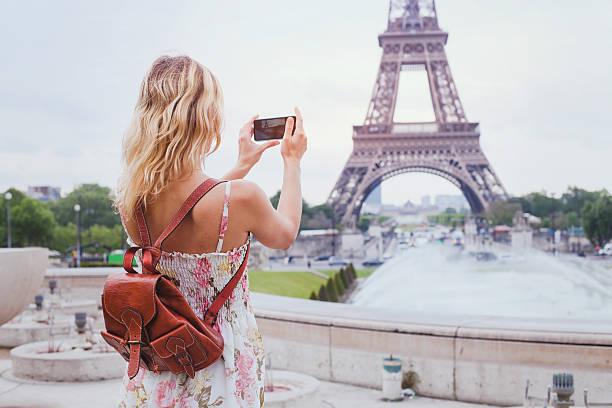 tourist taking photo of eiffel tower in paris - ikonische frauen stock-fotos und bilder