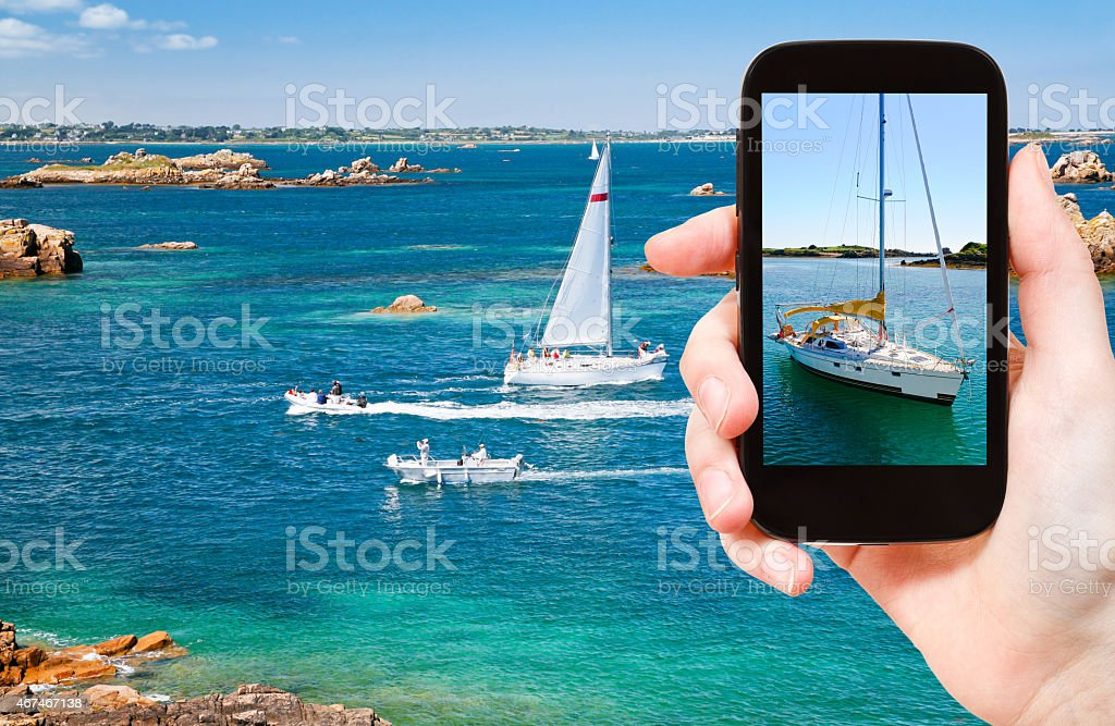 tourist taking photo of yacht near Brittany stock photo