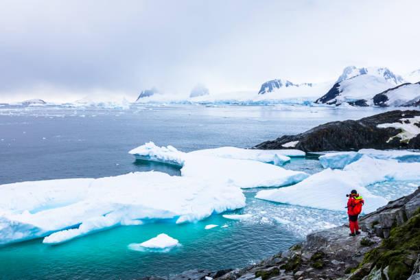 Tourist fotografiert erstaunliche gefrorene Landschaft in der Antarktis mit Eisbergen, Schnee, Bergen und Gletschern, schöne Natur auf der Antarktischen Halbinsel mit Eis – Foto