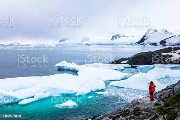 Photo of Tourist taking photos of amazing frozen landscape in Antarctica with icebergs, snow, mountains and glaciers, beautiful nature in Antarctic Peninsula with ice