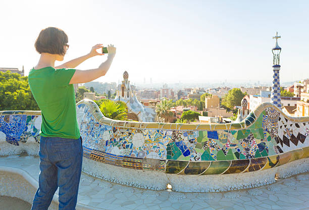 Tourist taking photos with smartphone in Gaudi's Park Guell, Barcelona Barcelona cityscape seen from Park Guell. gracia baur stock pictures, royalty-free photos & images