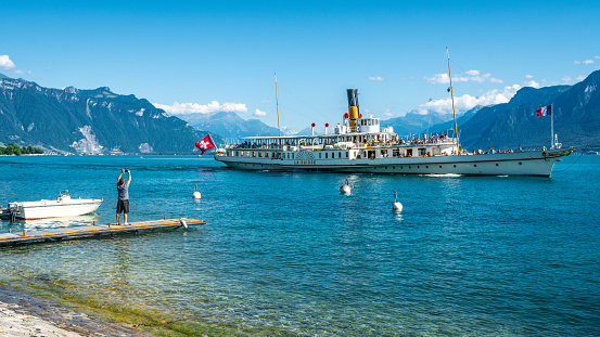 Tourist taking picture from lakeside of La Suisse a touristic vintage paddle steamboat sailing on Lake Geneva in Vevey Switzerland