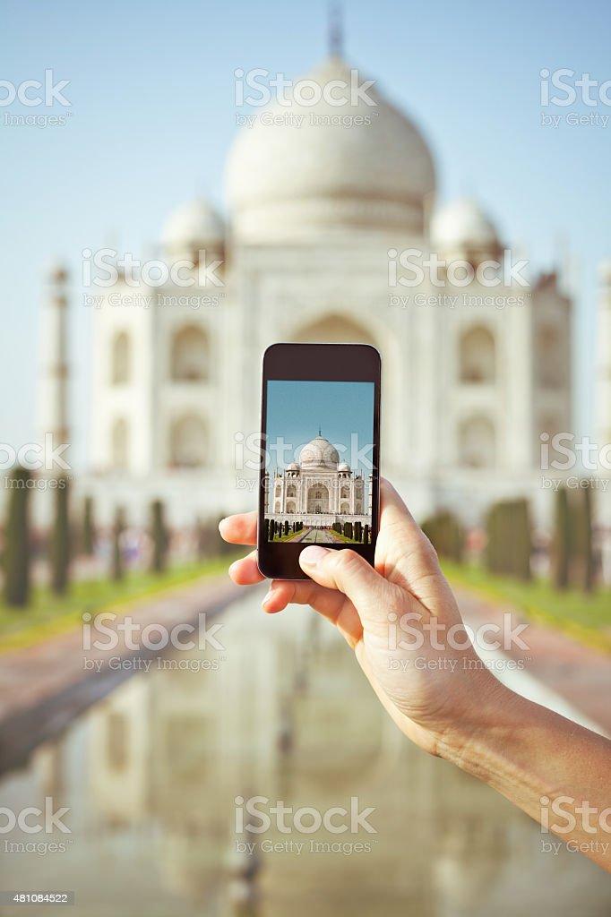 Tourist taking picture of Taj Mahal using smart phone Toursit taking picture of Taj Mahal in India using smart phone. Close up of phone and hand. Unrecognizable person. 2015 Stock Photo