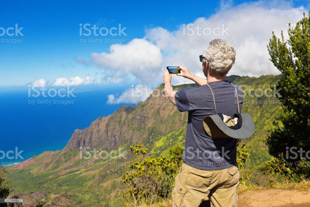 Tourist  Taking Picture with Smart Phone at Waimea Canyon State Park Kalalau, Kauai, Hawaii stock photo