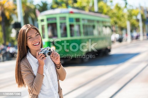Asian woman tourist -city street lifestyle, famous tramway cable car system in San Francisco city, California during summer vacation. Travel fun taking pictures with vintage camera.