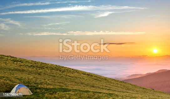 Tourist tent located in summer mountains at sunset. Hiking camp in evening nature. Travel and get away concept.