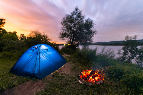 Tourist tent near the river. Campfire burning low. Early morning. Beautiful sunrise sky. stock photo