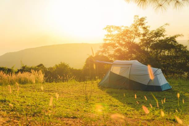 Touristisches Zelt auf der Wiese im Sonnenuntergang mit Blick auf die Berge. Camping im Freien – Foto