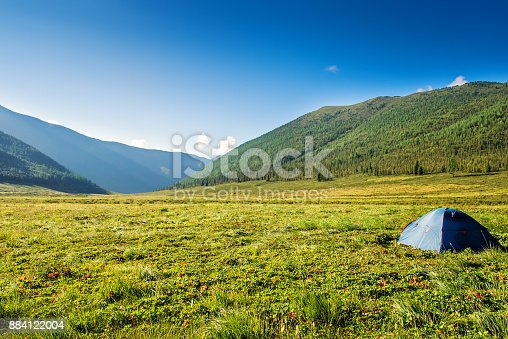 istock Tourist tent on mountain meadow field dawn sunrise 884122004