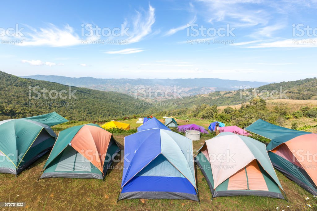 Tourist tents in camp among meadow on the mountain. stock photo