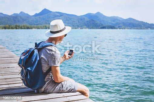 istock Tourist traveler using mobile phone, smartphone travel app. 1062129282
