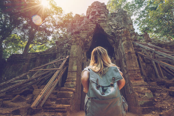Tourist traveling female stands in front of temple complex gate looking up at the sculpture on top, people discovery exploration concept stock photo