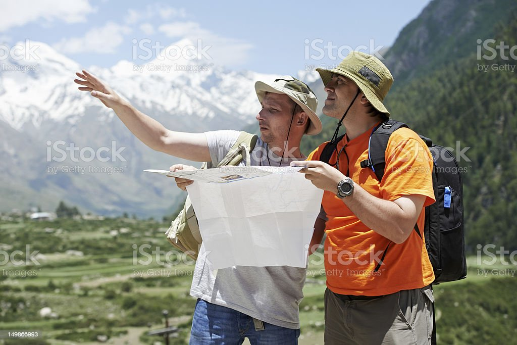 Tourist travellers with map in mountains stock photo