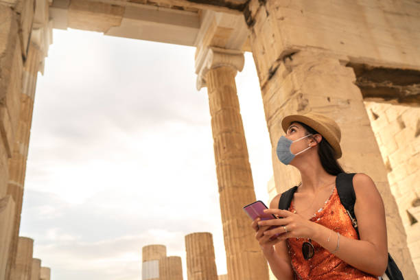 Tourist using face mask and using smartphone visiting ancient greek city stock photo