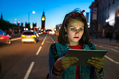 Young woman using digital tablet on street at night.