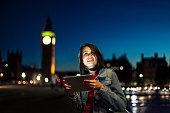 Young woman using digital tablet on bridge at night. Wears casual clothes.