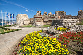 Tourist visiting ruins of Ancient Fortifications at the entrance of old town of Nessebar, Burgas Region, Bulgaria