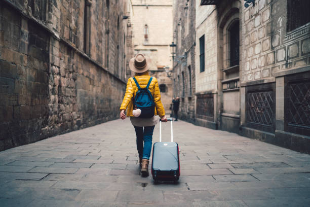 Tourist visiting Spain Young woman with suitcase walking at the street in Barcelona travel stock pictures, royalty-free photos & images