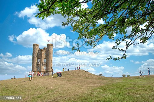 Tourist visiting the famous Broadway Tower on a lovely Summers day, sitting high in the Cotswold landscape. Broadway Tower is a folly on Broadway Hill, near the large village of Broadway and is the second-highest point of the Cotswolds (312m) after Cleeve Hill  (330m)