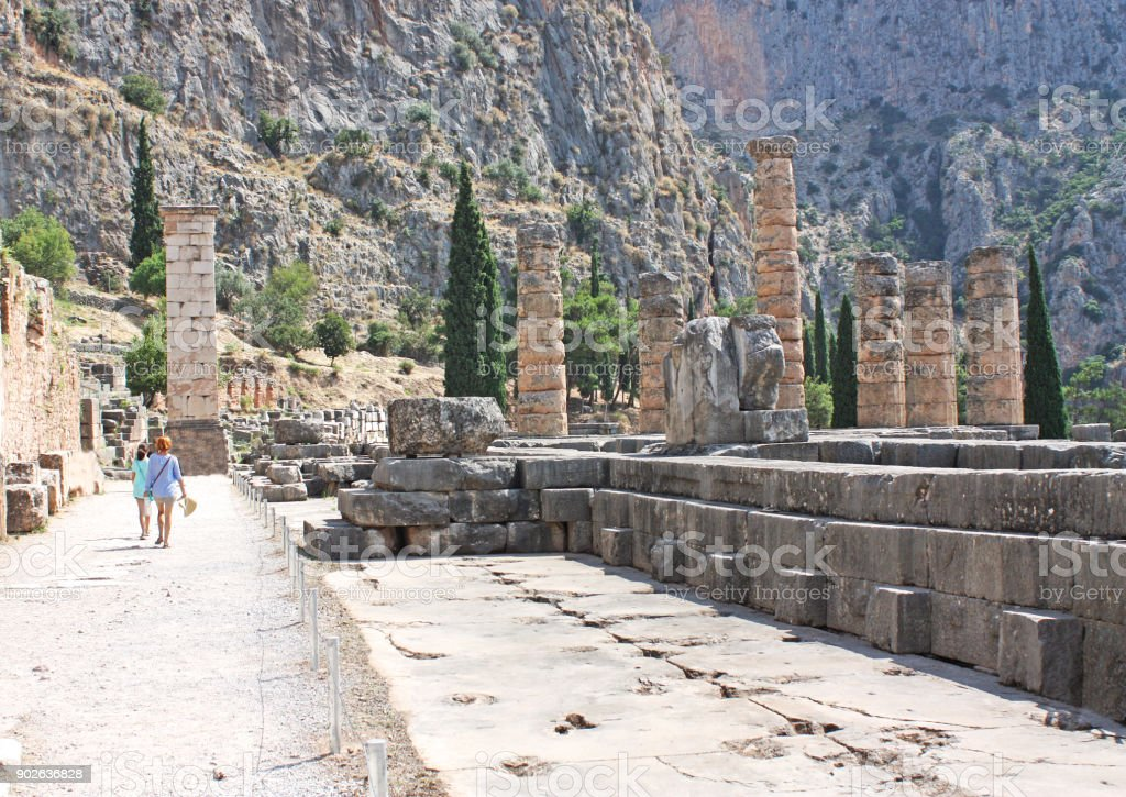 Tourist visits ancient Columns and ruins at Temple of Apollo, Delphi, Greece stock photo