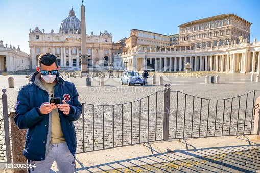 Vatican, Italy, March 11 -- A tourist protected by a medical mask in the square of St. Peter's Basilica closed to visitors and completely deserted, controlled by an Italian police patrol. In the background on the right the Apostolic Palace, seat of the Catholic Pontiff.