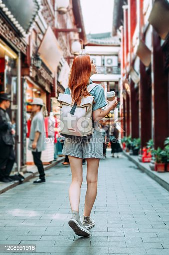 Female red hair tourist waliking in Chinese district in Shanghai, china. Asia tourism travel. Woman wearing travel backpack, sneakers and blue shirt and shorts in Tianzifan district