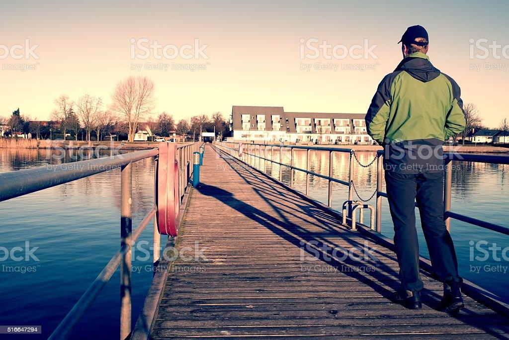 Tourist walk on pier to harbor. Calm water level stock photo