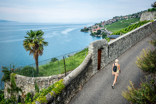 Tourist walking on a hiking path in middle of Lavaux terraced vineyards and Geneva lake view in Lavaux Vaud Switzerland