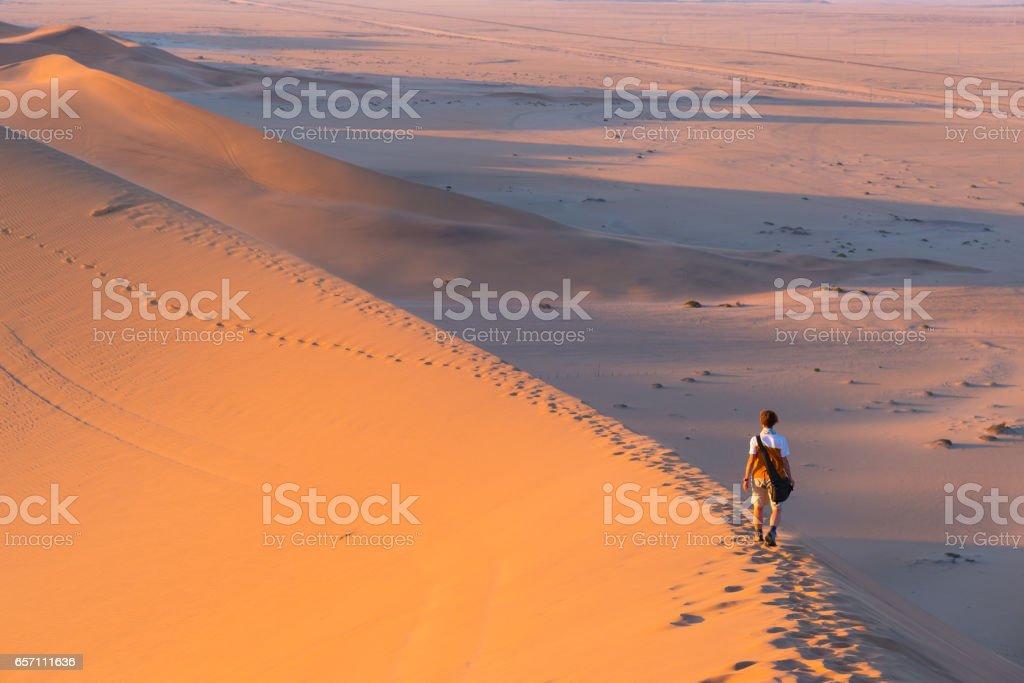 Tourist walking on the scenic dunes of Sossusvlei stock photo