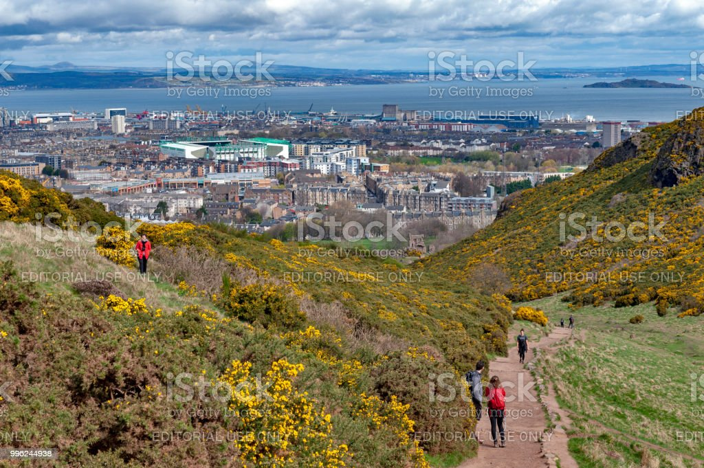 Tourist walking through grassy slopes of hills on a hillwalking route up to Arthur's Seat, the highest point in Edinburgh located at Holyrood Park, Scotland, UK stock photo