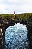 Tourist walks over a natural rock bridge connecting basalt cliffs in Arnarstapi, Iceland, with Atlantic Ocean in the background.