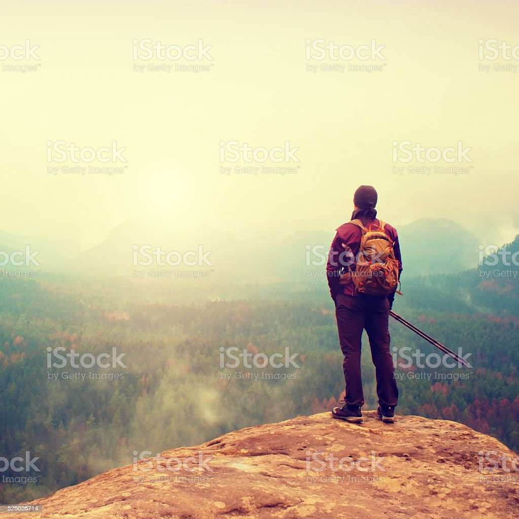 Tourist watching into deep misty valley bellow. Spring day stock photo