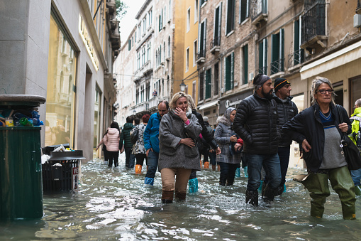 tourist wear boots and rain cover Flooded at central Venice not an unusual sight