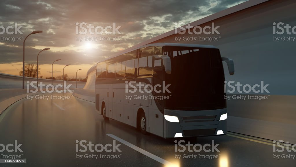 Tourist white bus driving on a highway at sunset backlit by a bright...