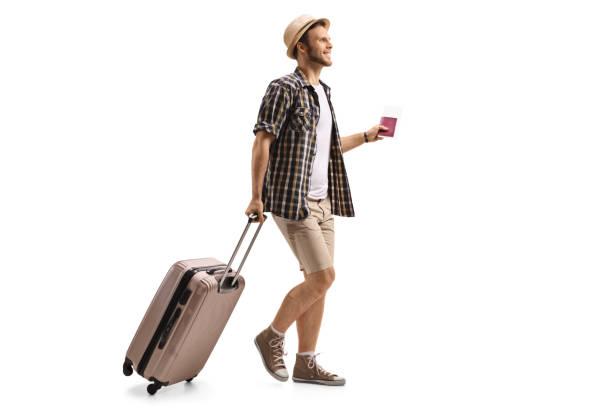 Turista con un pasaporte y una maleta caminando - foto de stock