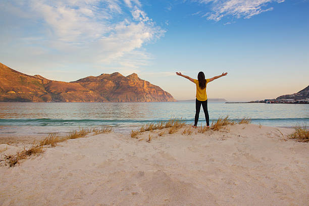 Tourist with arms up at Hout Bay beach at dusk Tourist holding arms up in the air at Hout Bay beach at dusk with sunlit mountain hout stock pictures, royalty-free photos & images