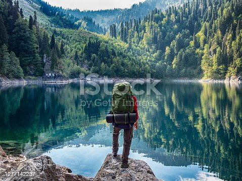 istock Tourist with backpack at mountain lake background 1277142237