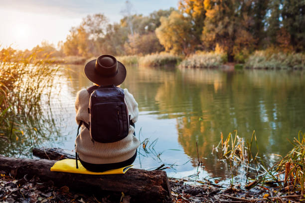 Tourist with backpack sitting on river bank at sunset. Middle-aged woman admiring autumn nature