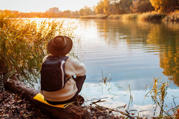 Tourist with backpack sitting on river bank at sunset. Senior lonely woman relaxing and admiring autumn nature