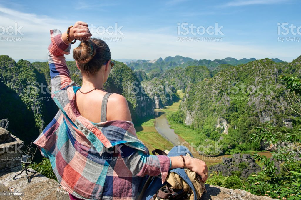 tourist with backpack sitting on top of the mountain enjoying river and valley view. stock photo