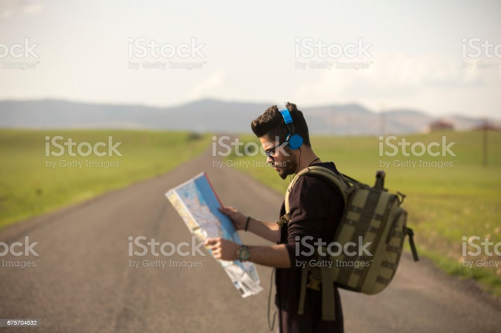Tourist with beard laughing and holding a map royalty-free stock photo