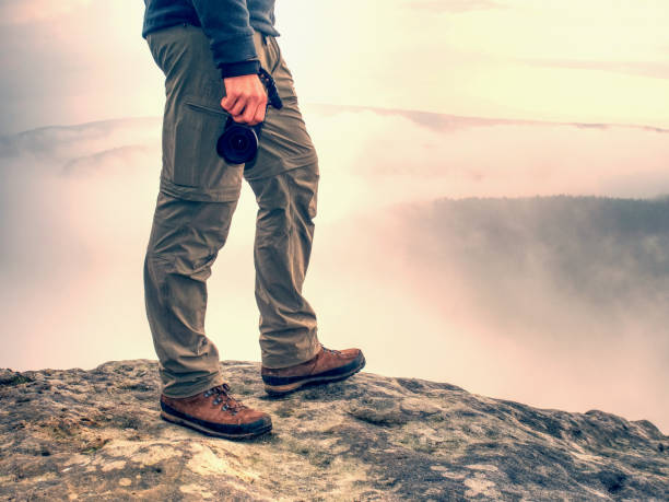 Tourist with camera in hand stays in trekking trousers and brown boots. stock photo