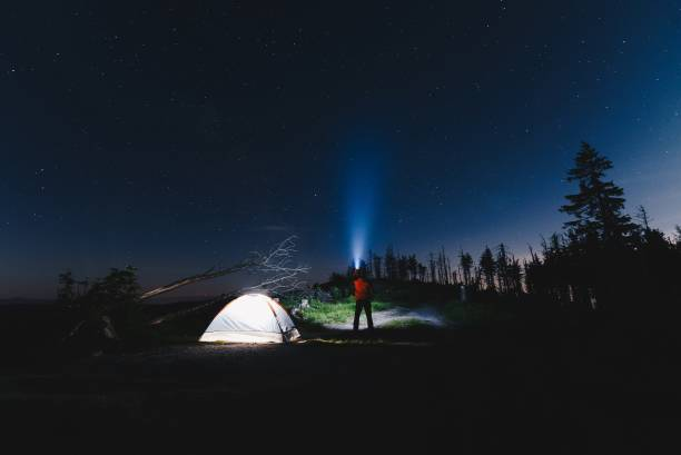 Tourist with flashlight near his camp tent at night stock photo