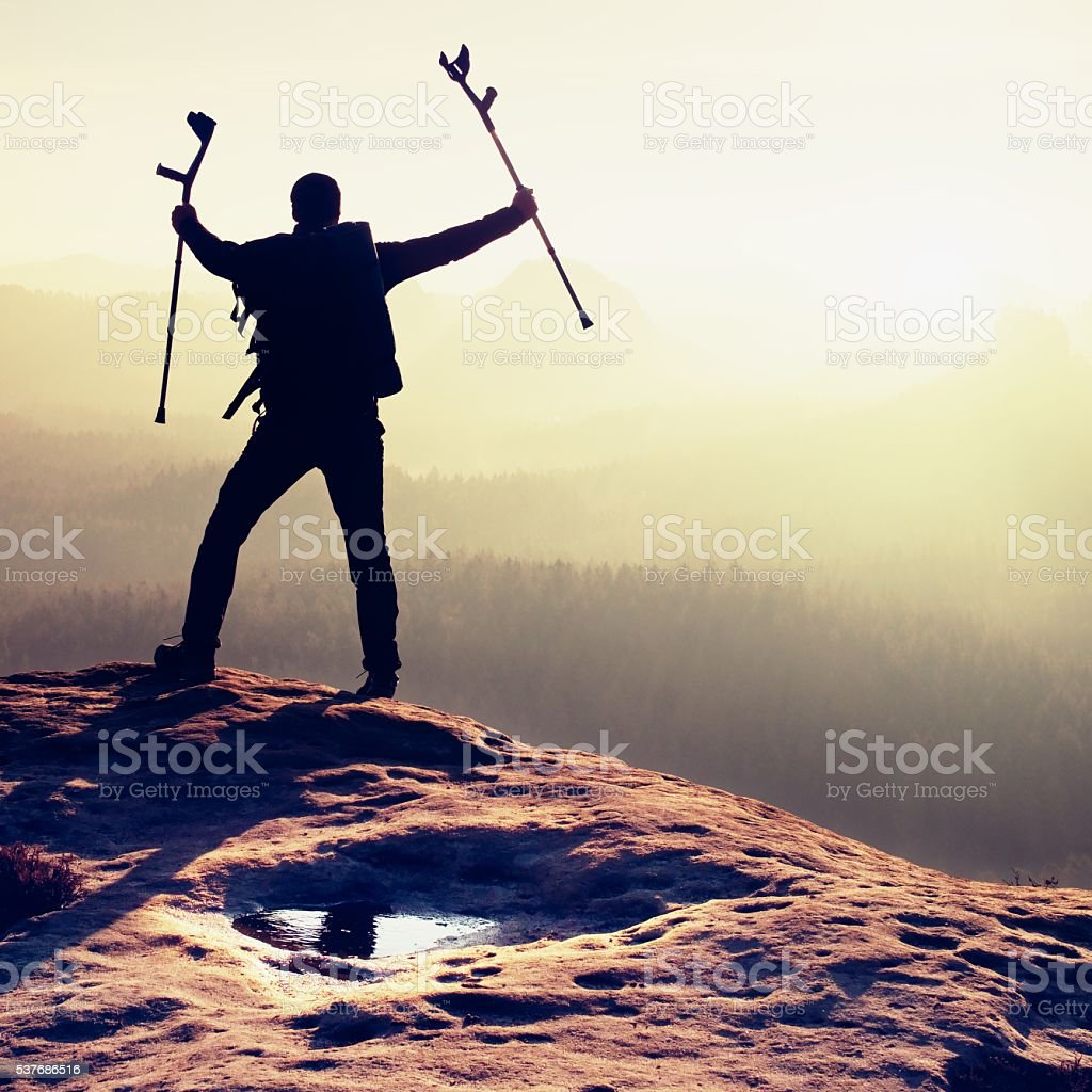 Tourist with immobilizer and medicine crutch achieved mountain peak stock photo