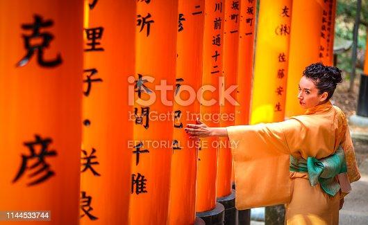 29 march 2019 - Kyoto, Japan: Tourist woman dressed with kimono touching a torii in Fushimi inari Taisha shrine