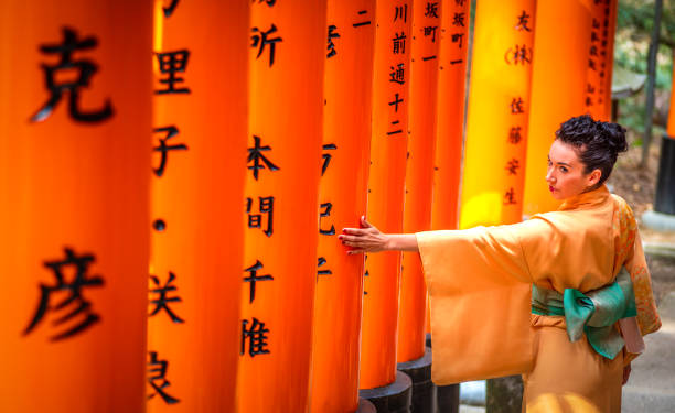 tourist with kimono touching a torii in Fushimi inari taisha, Kyoto, japan 29 march 2019 - Kyoto, Japan: Tourist woman dressed with kimono touching a torii in Fushimi inari Taisha shrine torii gate stock pictures, royalty-free photos & images