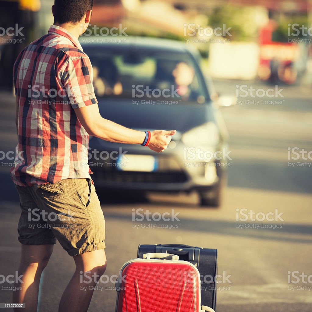 Tourist with luggage hitchhiking on the way stock photo