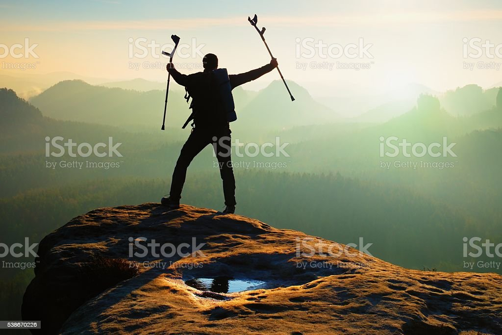 Tourist with  medicine crutch above head. Hiker with broken leg stock photo