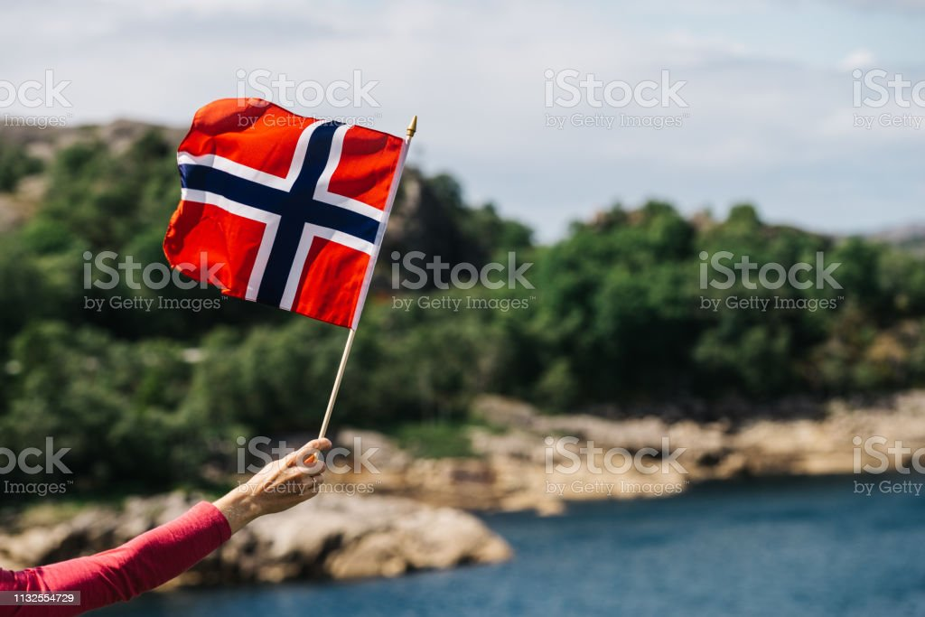 Tourist with norwegian flag on sea coast