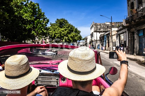 Tourist With Straw Hats Enjoying Cuba In Vintage Car